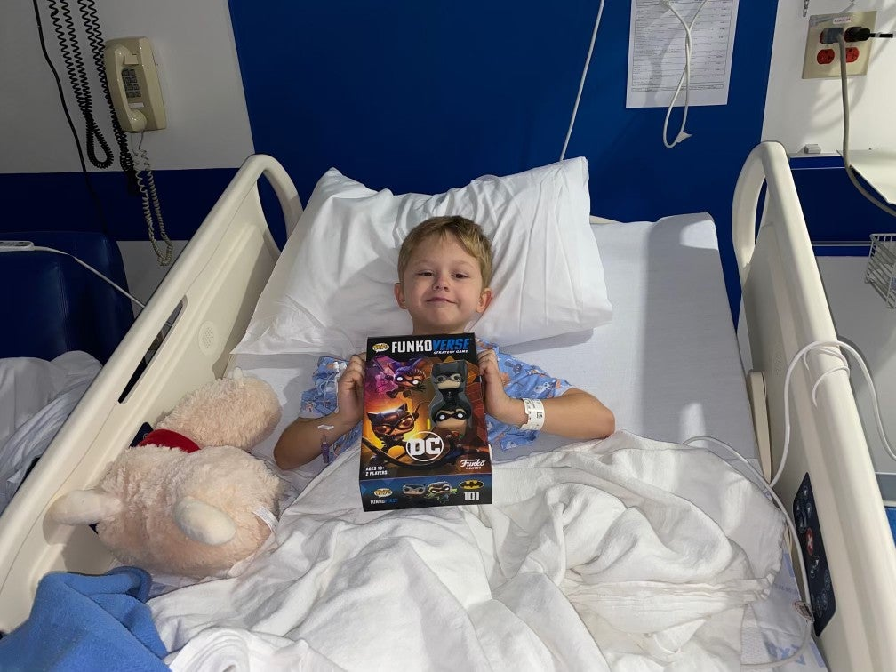 a photo of a smiling kid in a hospital bed, holding up a DC comics FunkoPop box