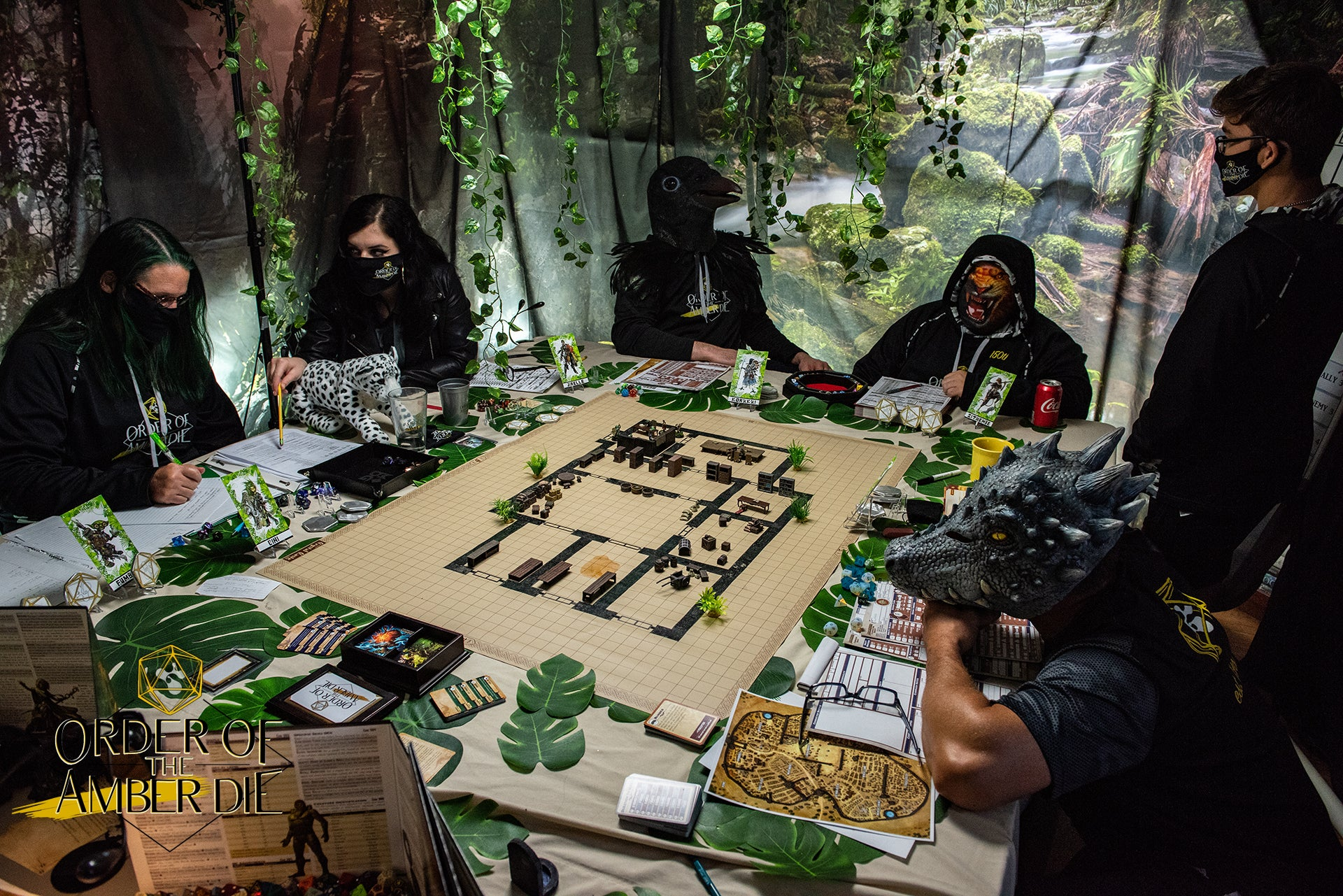 The order of the Amber Die, all wearing masks, sitting around the gaming table