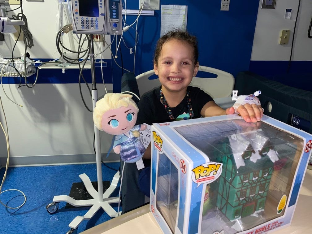 a photo of a smiling kid in a hospital room with an Elsa doll and Funko Pop figure