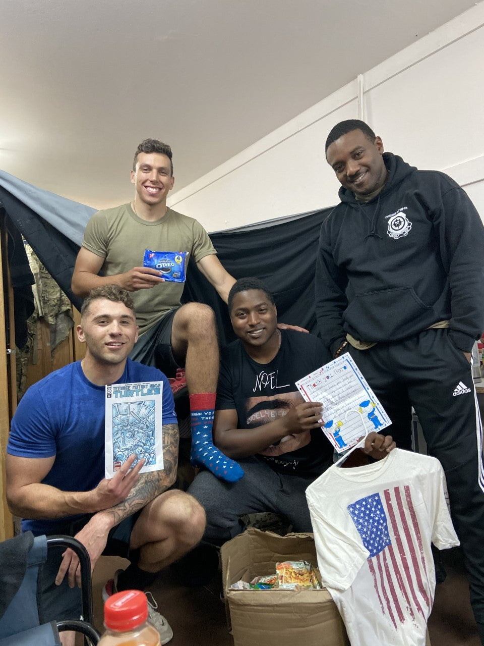 Four soldiers posed with a stack of comics and snacks