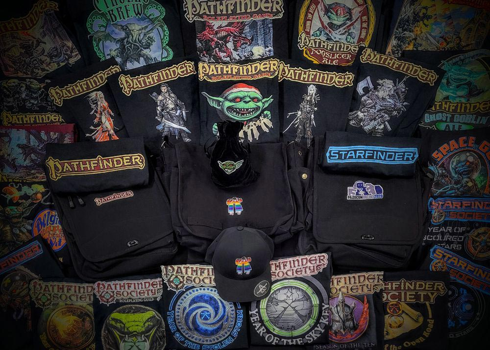 Off World Design's Paizo branded merchandise, Pathfinder and Starfinder Logo T-shirts, a goblin dice bag, Paizo's pride golem on a black messenger bag and black baseball cap.