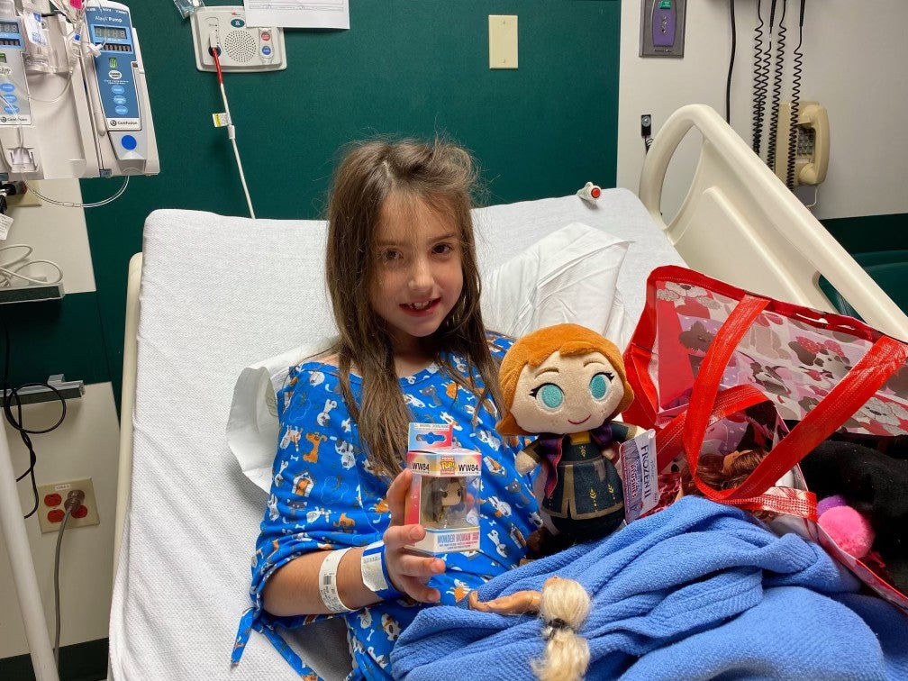a photo of a smiling kid in a hospital room with an Anna doll and Funko Pop figure