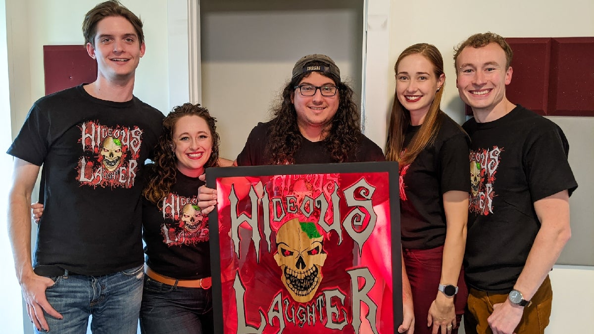 The team behind Hideous laughter productions standing for a group photo holding a sign with their skull shaped logo in the center