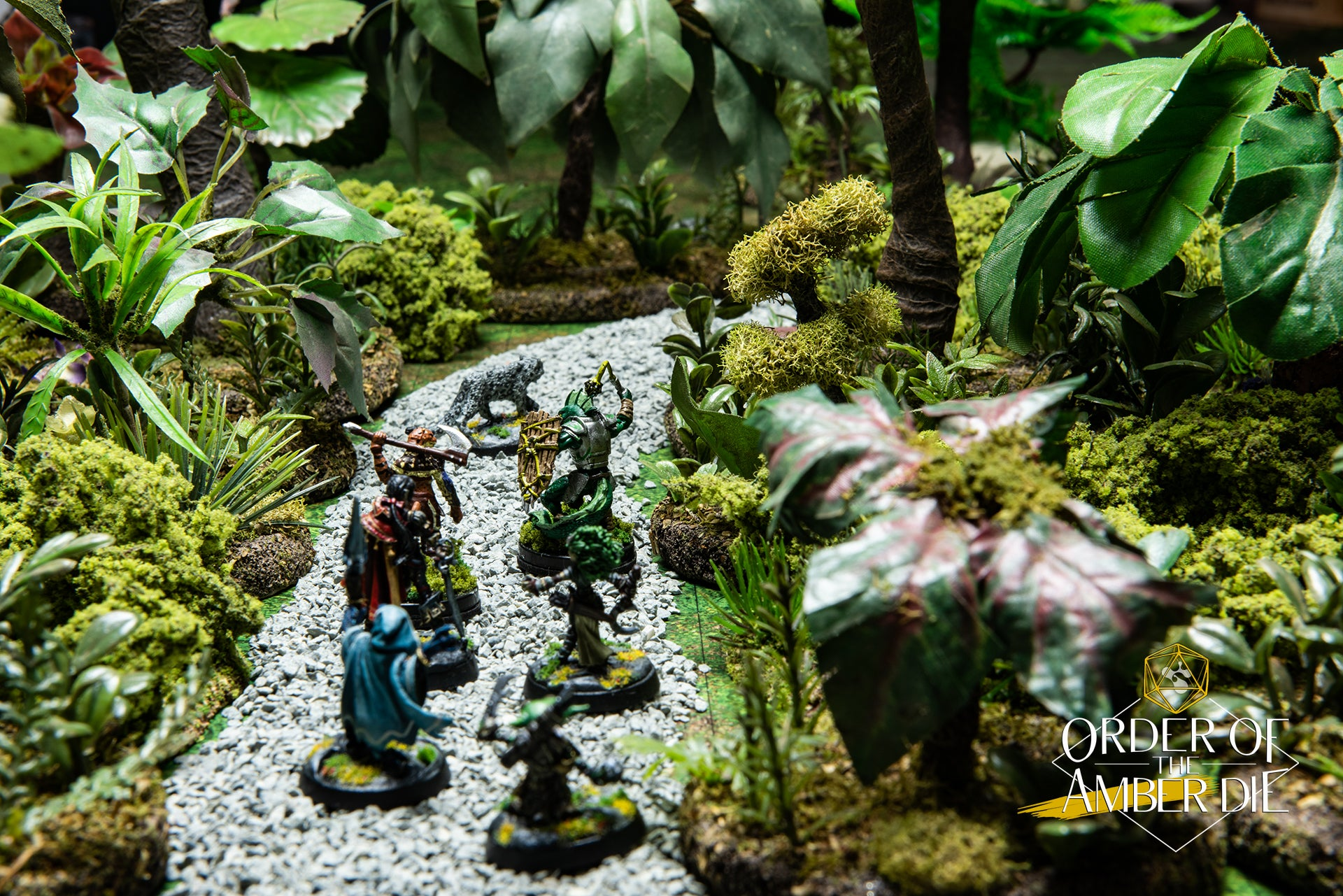 The players mini figures on a path through a densely wooded jungle map