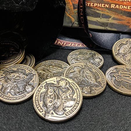 A close-up of the Fumbus coins from the first picture. They are a brassy looking coin with Fumbus the goblin engraved on them. Above him, the word Pathfinder curves along the edge of the coin. Below him, the words Second Edition 2019.