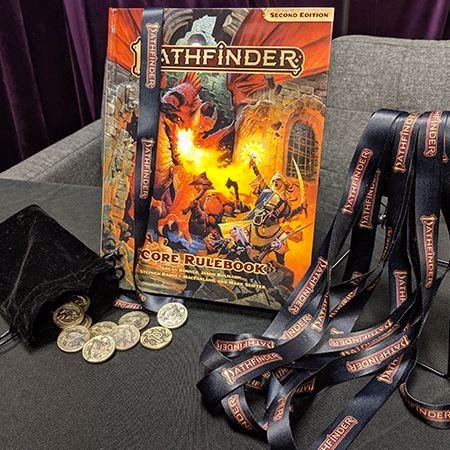Three items on a grey fabric surface. On the left, an open dicebag with shiny Fumbus coins spilling out. In the center, the Pathfinder 2E core rulebook. On the right, a number of Pathfinder lanyards.