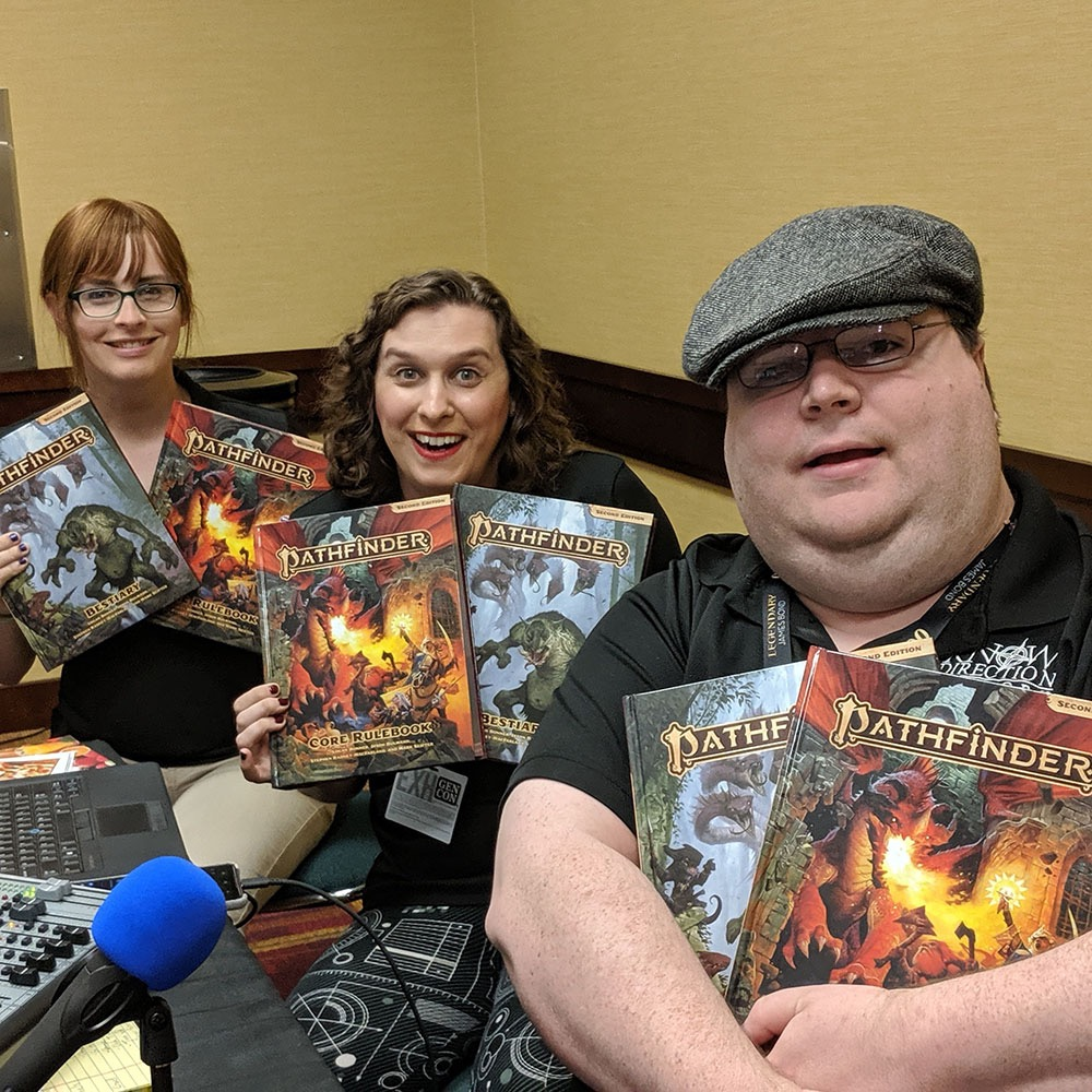 Picture of 3 people showing off their Pathfinder rulebooks.