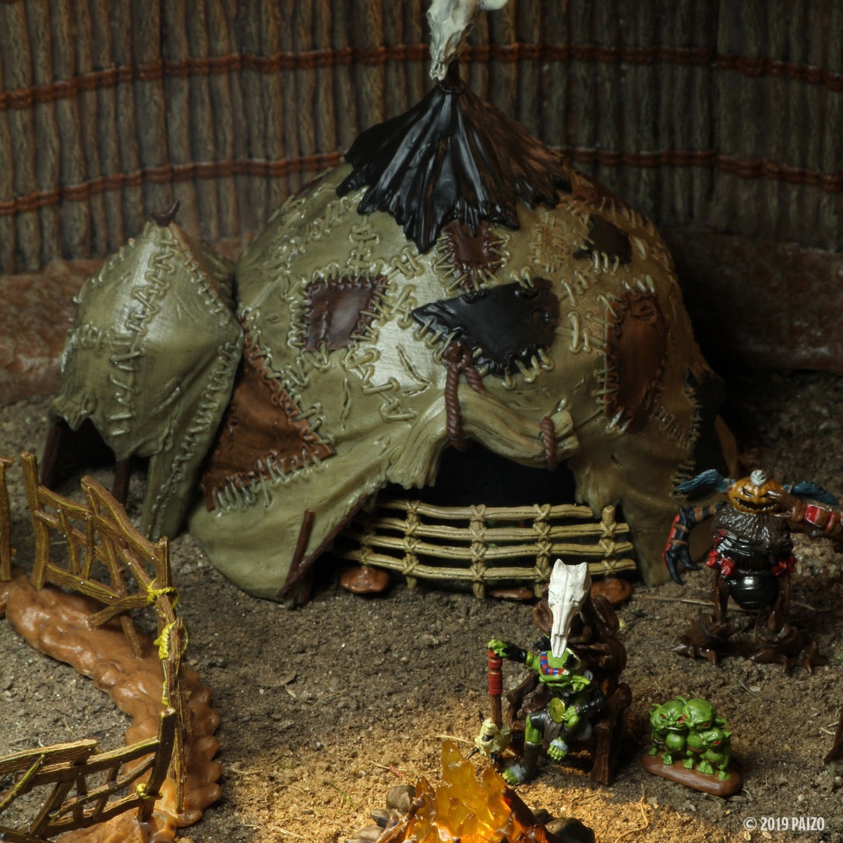 A closeup of a goblin village, focused on a large goblin tent with a gate across the opening.
