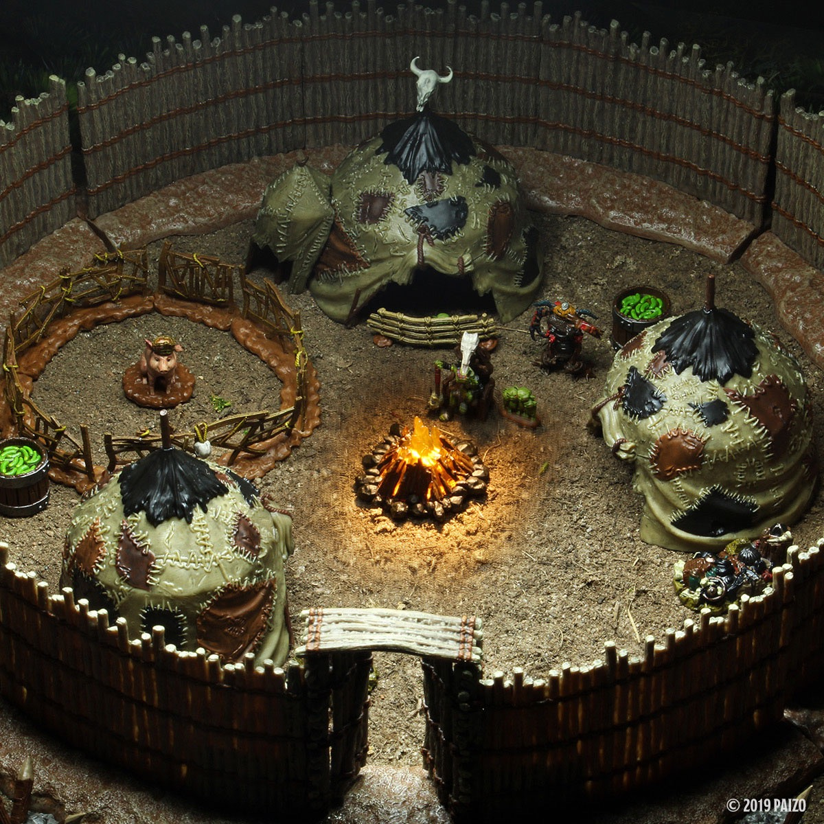 Three goblin tents sit inside a circular gated area. The gating is made from long wooden poles. A bonfire is aglow in the center. A pigpen has been set up next o one of the tents and the magic pig sits in hte middle.